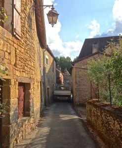 Yes, this is a truck squeezing through these buildings on this very narrow road in our village.