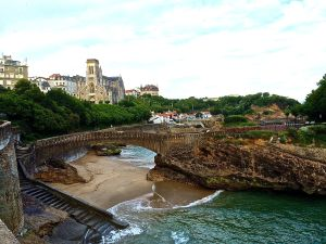 Rocky shoreline in Biarritz with St. Eugenie church in background.