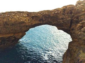 Craggy archway with Atlantic Ocean underneath in Biarritz.