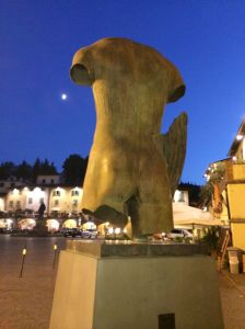 "This sculpture anchors one point on the Greve triangular main square.  We caught him ""mooning"" on this evening stroll with our gelato."