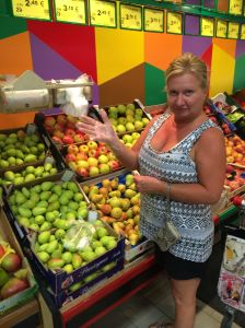 Rita demonstrating her compliance with local rules regarding the wearing of plastic gloves when squeezing the melons and handling other fruits and vegetables.  All the fashionable women are wearing plastic gloves this season in Italy.